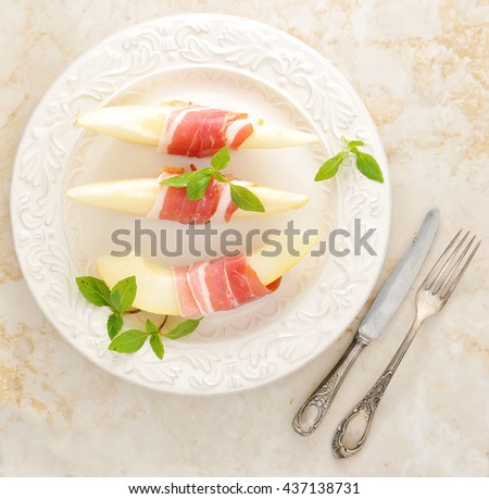 Becon and melon. Ham. Traditional Spanish dish - jamon Serrano and prosciutto crudo sliced with melon. Top view. Closeup.