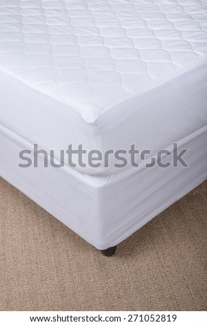 Bed corner with white sheet - stock photo