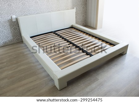 Bed in bedroom with wooden slats without mattress