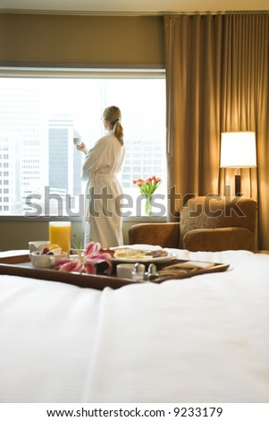 Bed in breakfast tray laying on bed with mid-adult woman in background. - stock photo