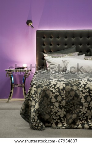 Bed in front of a purple wall - stock photo