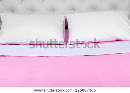 Bed in pink bed linen in room - stock photo