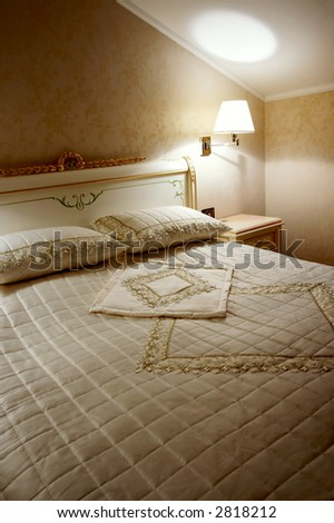Bed, lamp and bedside-table in a hotel room - stock photo