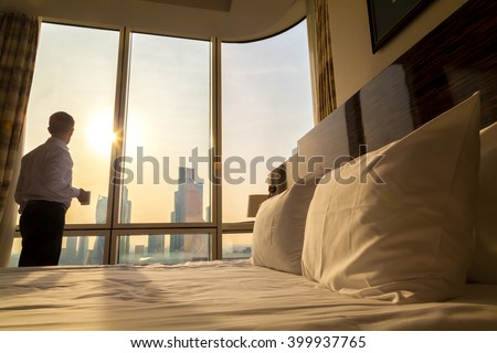 Bed maid-up with white pillows and bed sheets in cozy room. Young businessman with cup of coffee standing at window looking at city scenery on the background. Focus on cushion. Motivation concept - stock photo