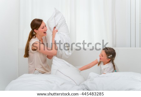 bed pillow fightng family on weekend - stock photo