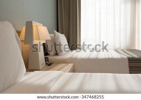 Bed room with white pillows , sheets and curtain with sunlight shining through the sparse curtain. - stock photo