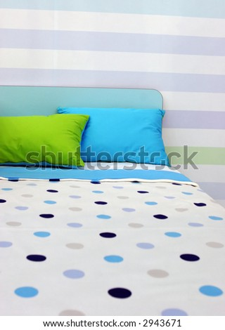 Bed with bright blue and green linen - home interiors - stock photo