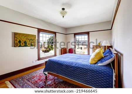 Bed with bright blue bedding and yellow pillows.