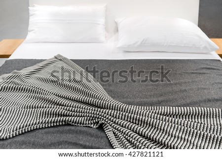Bed with gray striped cover and white pillows