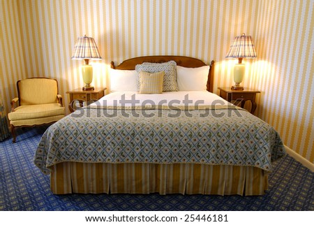 Bed with headboard, lamps and chair - stock photo