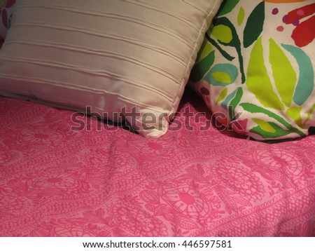 Bed with pink cover and two pillows - stock photo