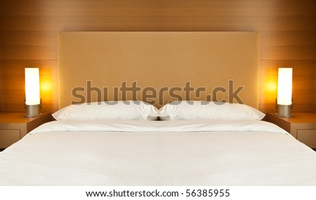 Bed with white sheets and two lamps (close-up) - stock photo