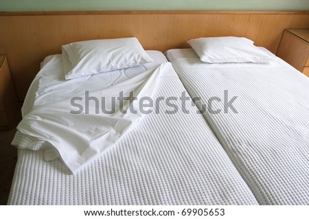 bedclothes and pillows of twin beds in a ordinary hotel room