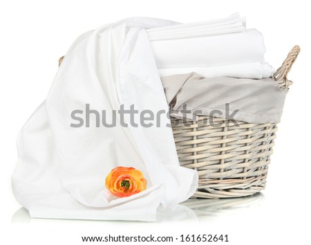Bedding sheets in wicker basket isolated on white - stock photo