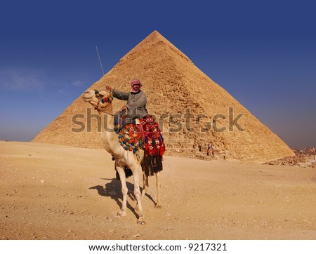 Bedouin and camel in front of the Great Pyramid at Giza - stock photo