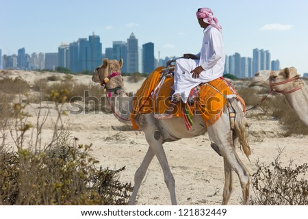Bedouin on a camel in the desert and a modern city on the horizon - stock photo