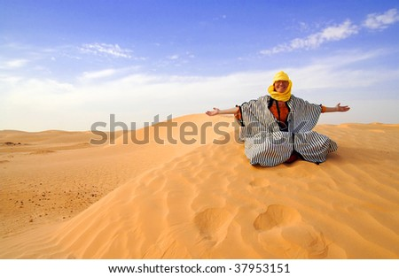 Bedouin styled woman is sitting on the sand dune.