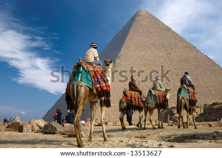 bedouins on camel near of great pyramid in egypt - stock photo