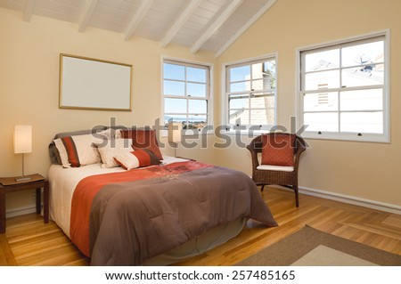 Bedroom decorated in red and brown bedspread with view window and armchair.  - stock photo