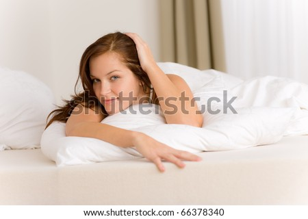 Bedroom - happy woman in white bed waking up