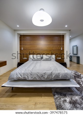 Bedroom in a modern style with light walls. There is a big bed with gray bedcover and pillows. On the both sides of the bed there are dark wooden bedside tables. On the back wall there is a big niche