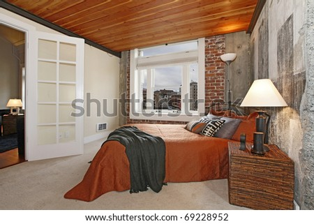 Bedroom in Modern City Apartment with wood ceiling and city view. - stock photo
