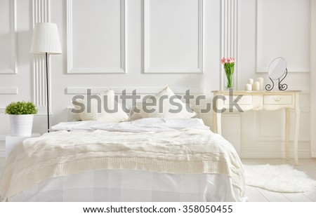 bedroom in soft light colors. big comfortable double bed in elegant classic bedroom - stock photo
