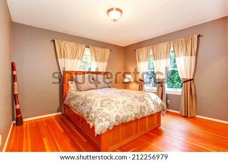 Bedroom in soft mocha color with curtains and wooden bed