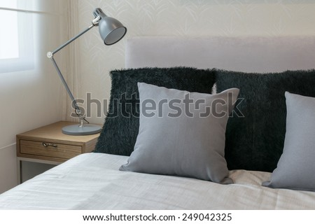 bedroom interior design with grey pillows on white bed and decorative table lamp. - stock photo