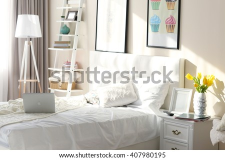 Bedroom interior in light tones with furniture and pictures on the wall - stock photo