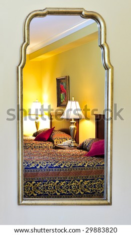 Bedroom interior reflected in mirror, image on the wall is my own. - stock photo