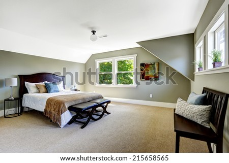 Bedroom interior with beige carpet floor and green walls. Furnished with wooden bed and  bench - stock photo