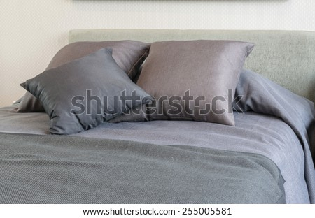 bedroom interior with grey pillows on bed and decorative table lamp. - stock photo