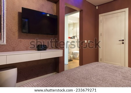 Bedroom interior with wall mounted and a view to a bathroom