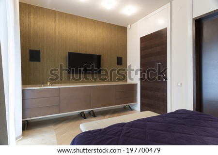 Bedroom interior with wall mounted tv and speakers - stock photo