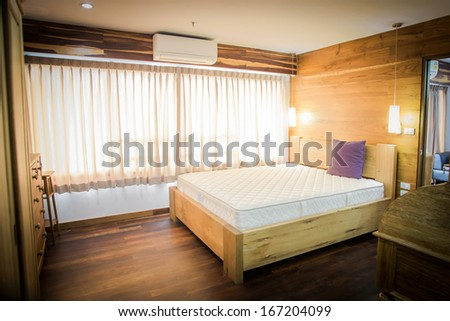 bedroom interior with white bedding and hardwood floor - stock photo