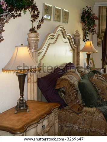 Bedroom scene of dressed bed and night stand. The décor is French stye and is heavy and ornate. The furniture is light in color and the tapestry bedding is in tones of gold, burgundy and green - stock photo