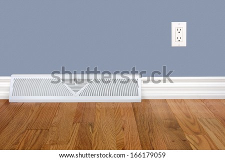 Bedroom wall with heating register, electrical outlet and hardwood floor - stock photo