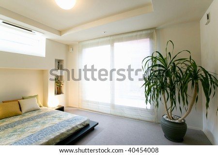 Bedroom with a big window and a plant.