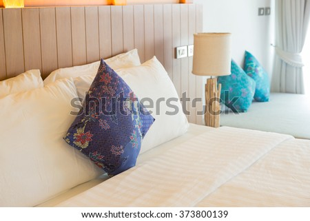 Bedroom with a pillow and blanket on the bed. The lamp is located at the top of the bed. - stock photo