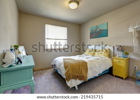 Bedroom with antique bed, yellow nightstand and turquoise cabinet