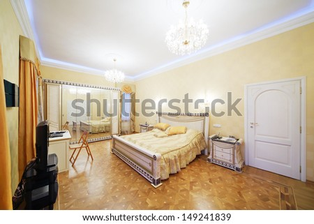 Bedroom with beautiful bed, tv, mirrorlike wardrobe in classic style.