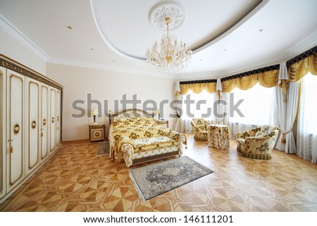 Bedroom with beautiful double bed, wardrobe and armchairs in classic style. - stock photo