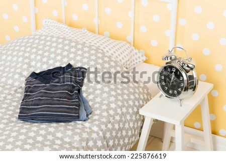 Bedroom with bed alarm clock and pajma for man - stock photo