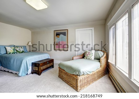 Bedroom with bed and wicker settee