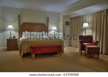 Bedroom with bedside tables armchair lamps and curtain