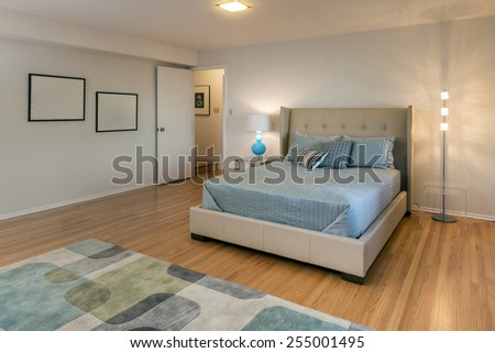 Bedroom with blue sheets, designer lights, pillows, night stands and wooden floor. - stock photo