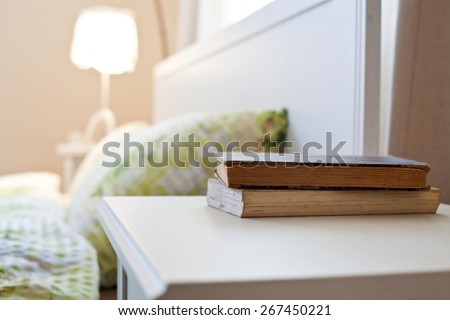 bedroom with books on nightstand - stock photo