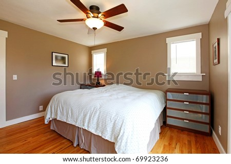 Bedroom with brown walls and blue blanket - stock photo