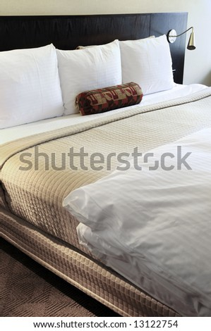 Bedroom with comfortable bed in neutral colors - stock photo